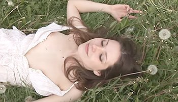 Young brunette posing in a flower field