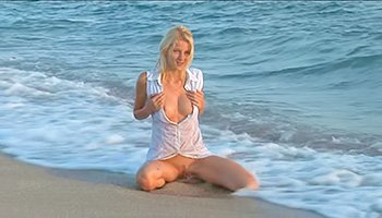 Blonde girl posing on a sunny beach