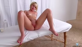 Oiled blonde is fingering pussy