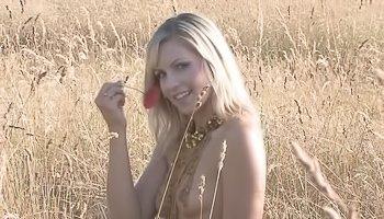 Sensual blonde is having solo in field