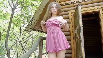 Blonde in dress is enjoying outdoors solo