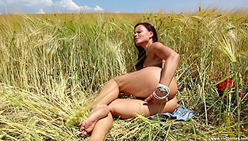 Stunning brunette masturbating in the field